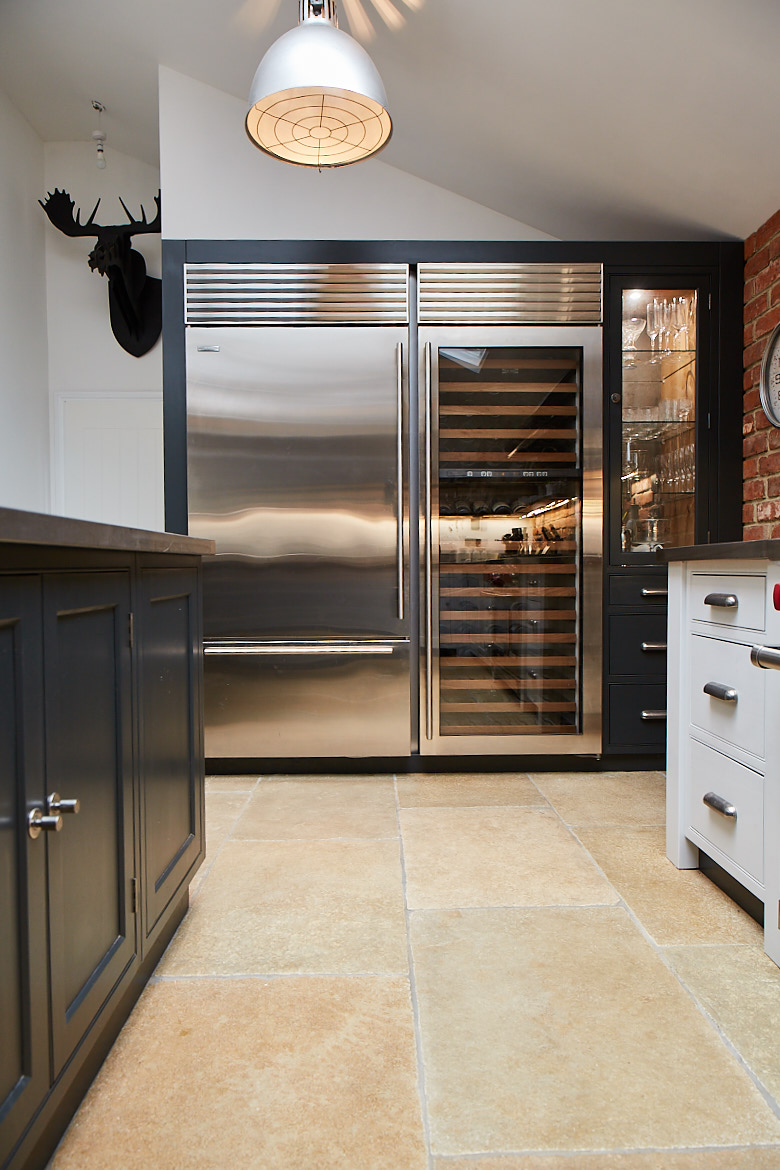 Large full height stainless steel Wolf wine fridge and fridge freezer next to bespoke painted cabinets