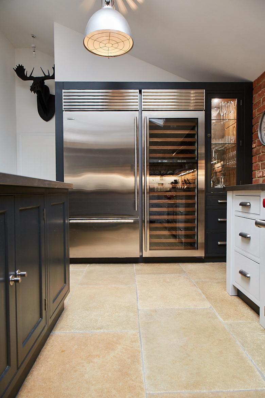 Large full height stainless steel Wolf wine fridge and fridge freezer next to bespoke painted cabinets