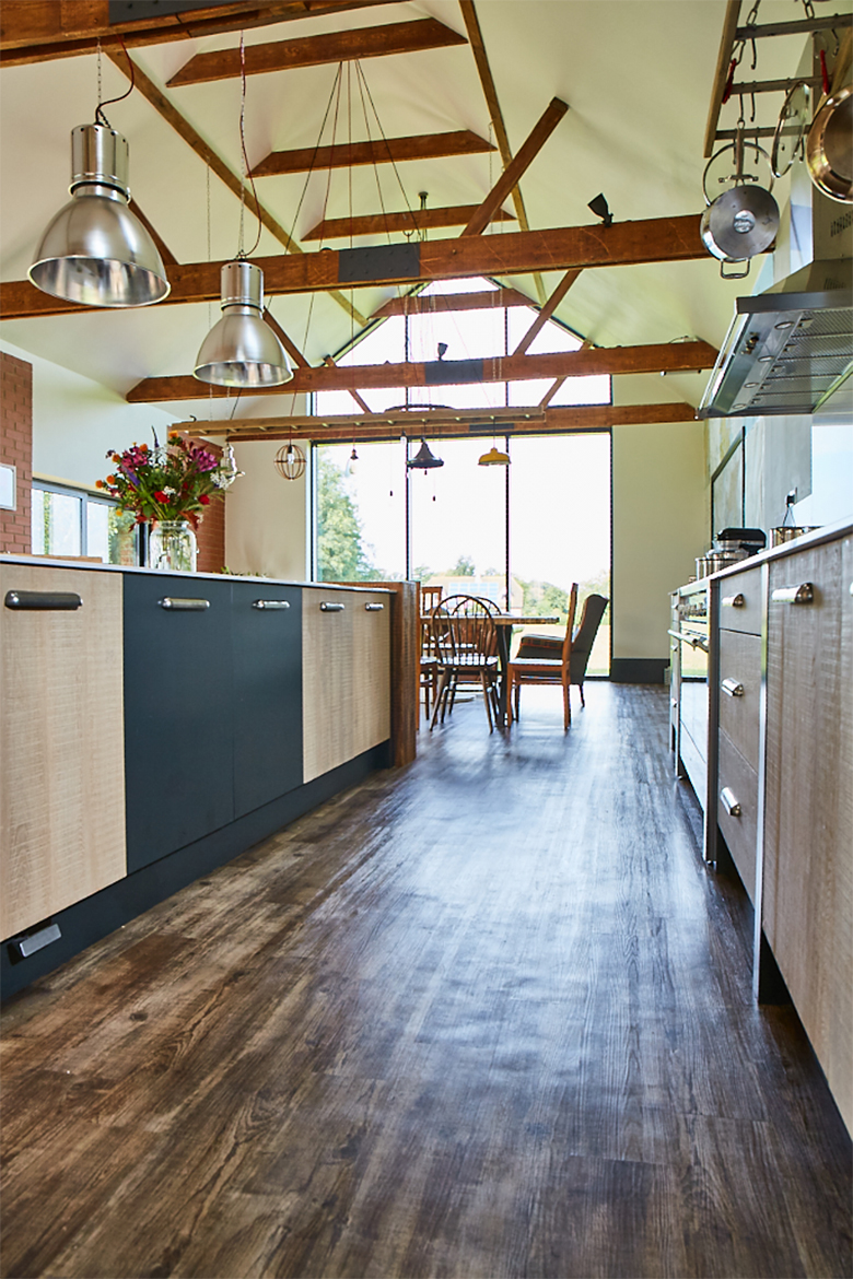 Reclaimed wood kitchen floor below high vaulted ceiling with exposed wood beams