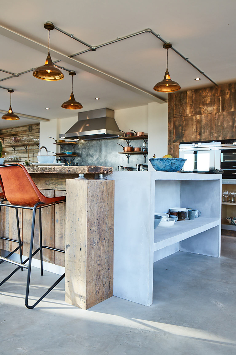 Reclaimed pine wood against grey washed bespoke kitchen concrete island end