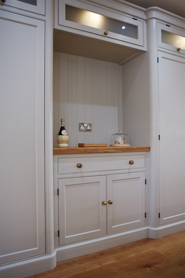 Bespoke kitchen cabinets painted in a light little greene colour with solid oak worktops and glazed wall cabinets