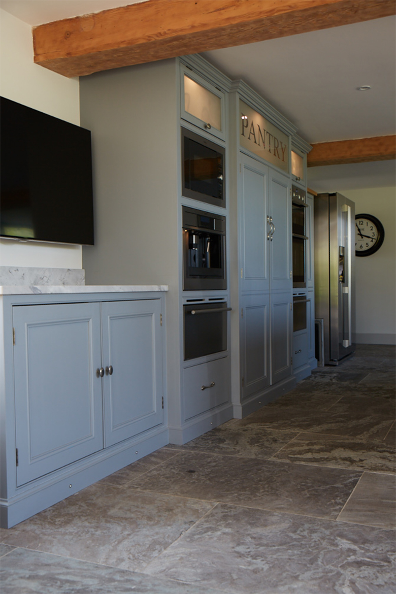 Tall bespoke kitchen units house integrated appliances with grey stone floor