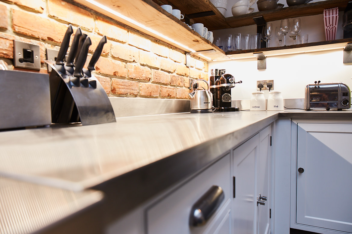 Close up of bespoke stainless steel worktop with knife block in background and finesse pewter handle