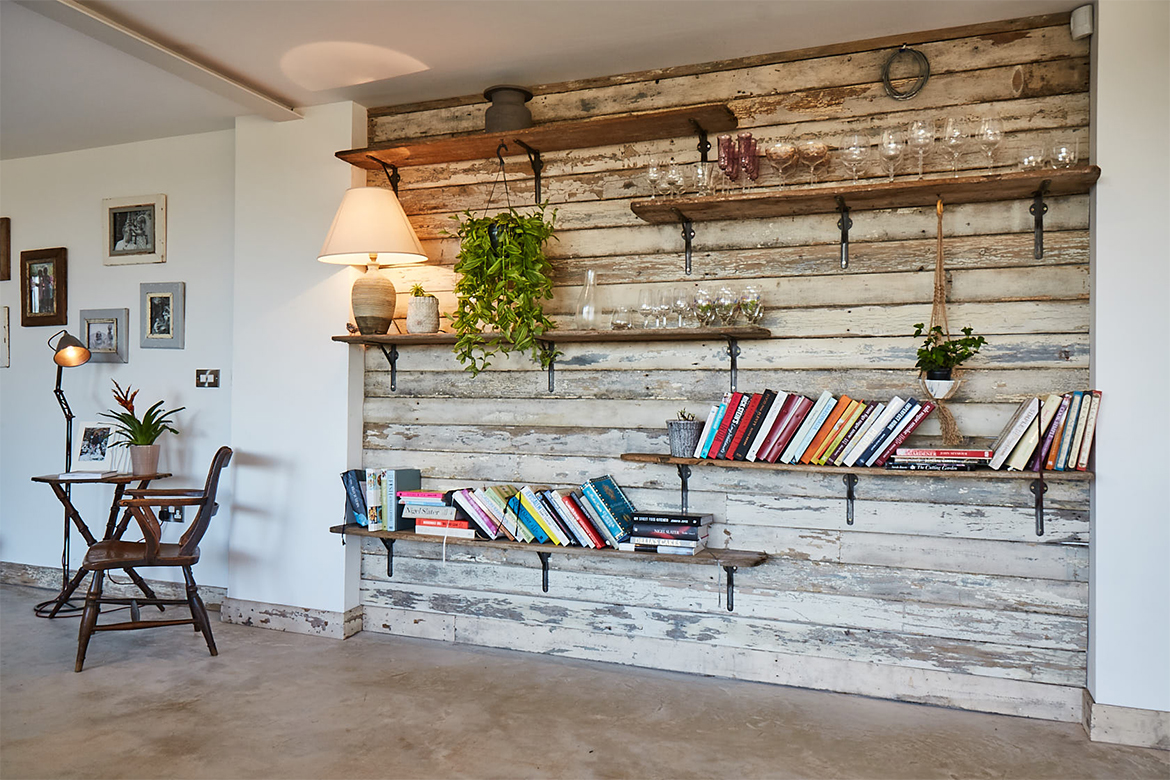 Flaky white reclaimed wall cladding with rustic bookshelves and cast brackets displaying cook books
