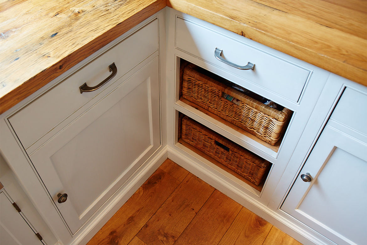 Bespoke painted corner unit with exposed wicker baskets reclaimed pine worktop and pewter pull handles