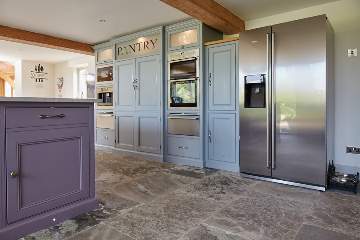 American stainless steel fridge sits beside tall painted integrated kitchen units
