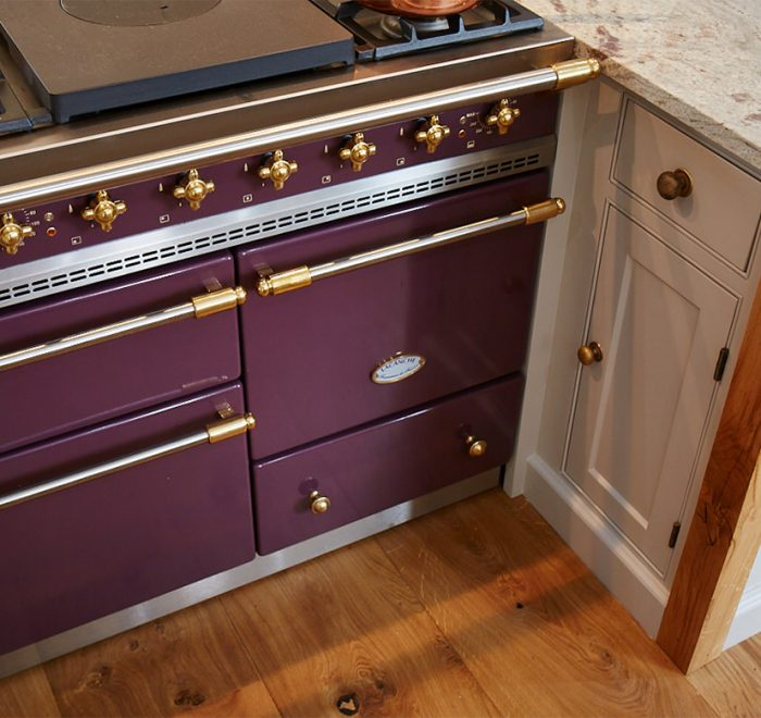 Classic plum macon lacanche with brass trim set in between painted bespoke cabinets with oak posts