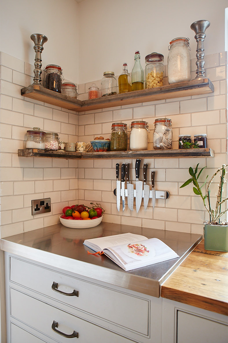Reclaimed oak shelves floating against white metro tiles with stainless steel worktop below on bespoke kitchen cabinet