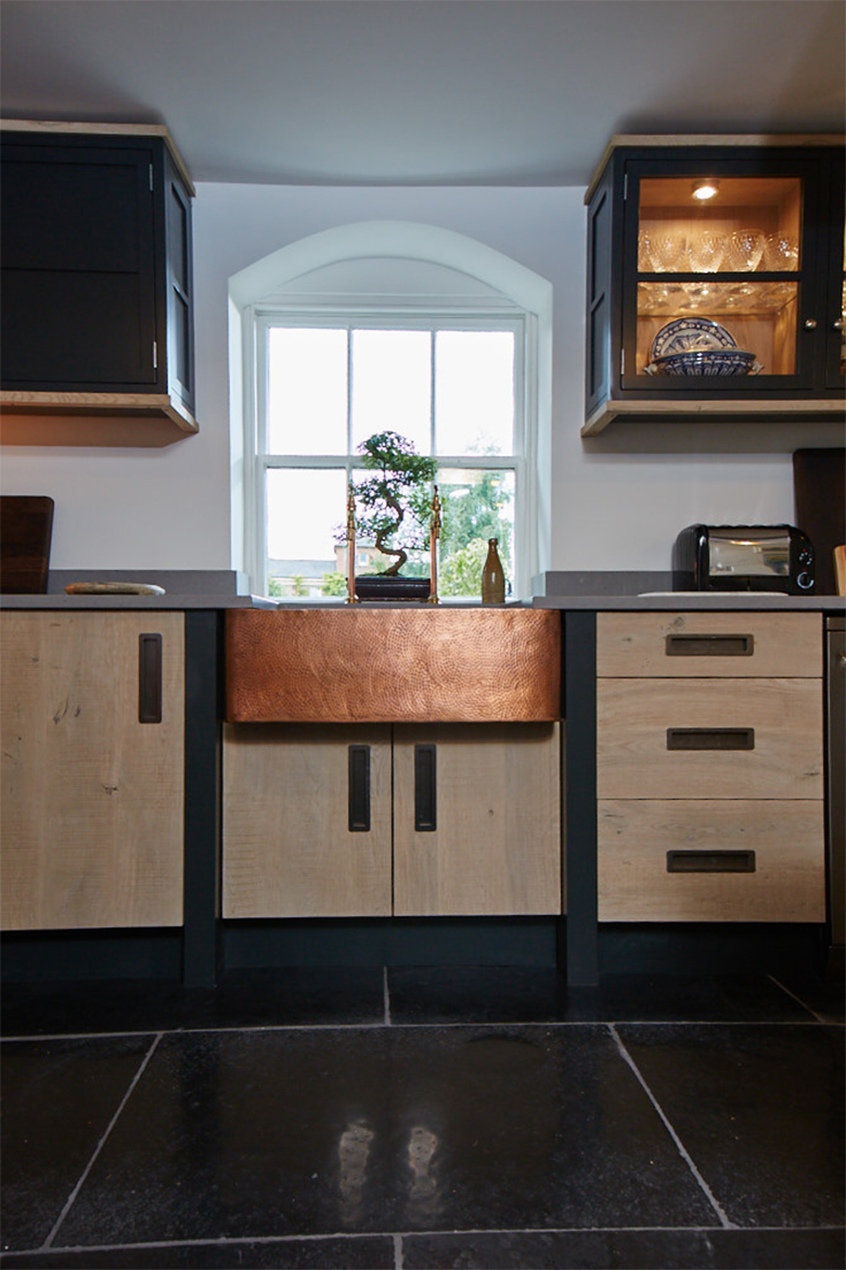 Bespoke engineered oak kitchen units with beaten copper belfast sink and dark painted posts