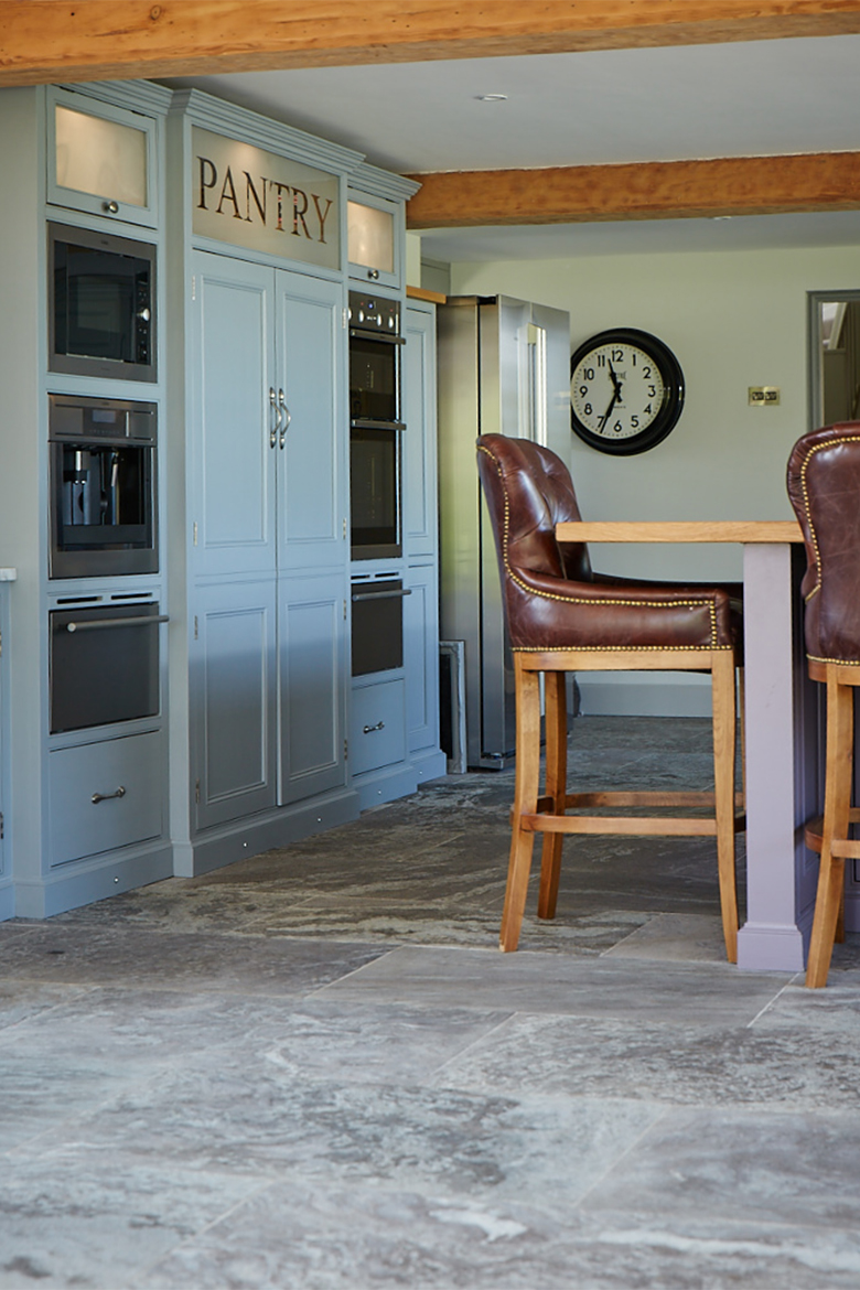 Leather bar stool sits in front of bespoke glazed painted pantry unit