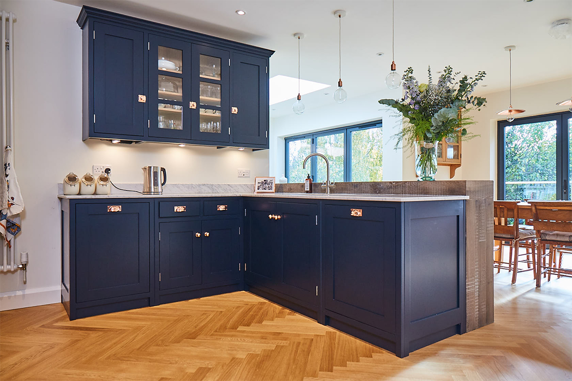 Blue kitchen cabinets in l configuration on oak parquet flooring
