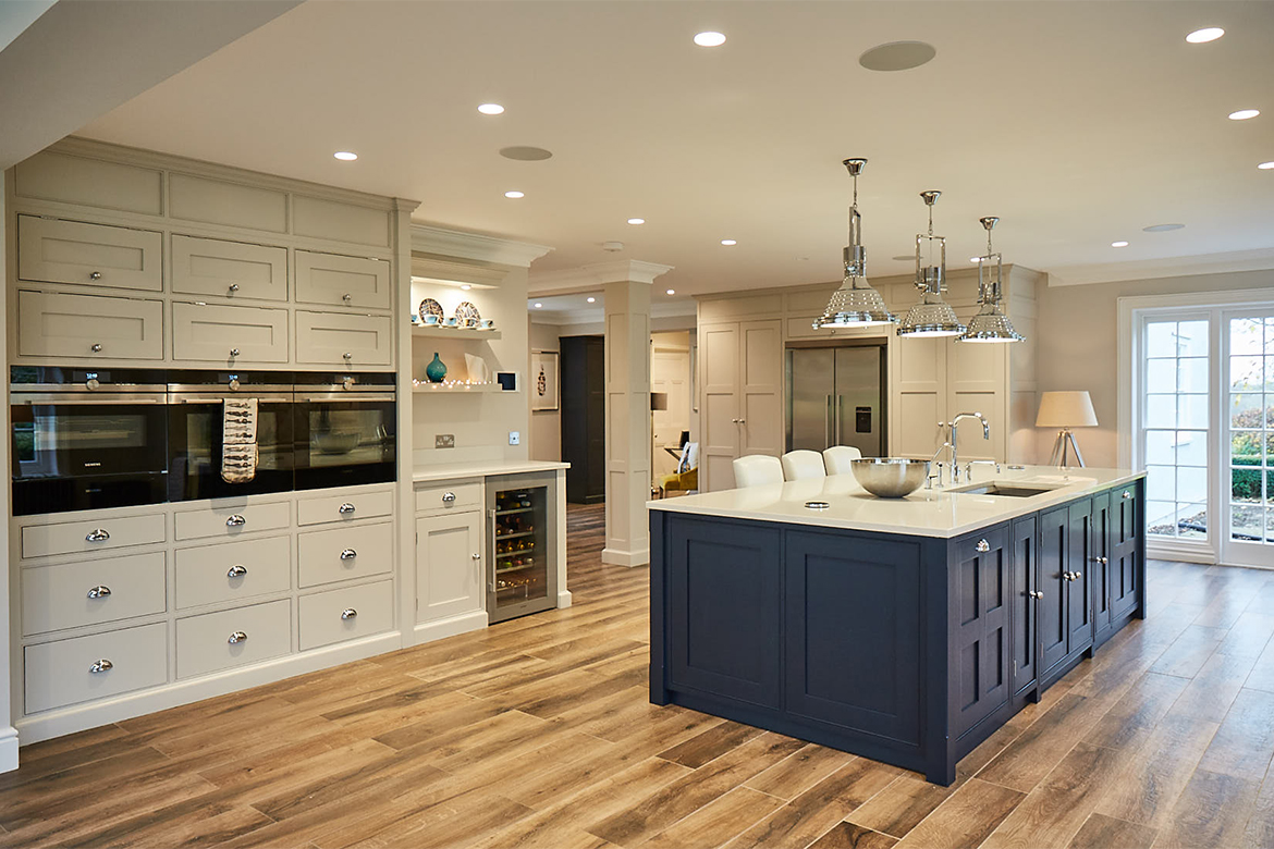 Bespoke kitchen island painted blue and tall oven units in light grey