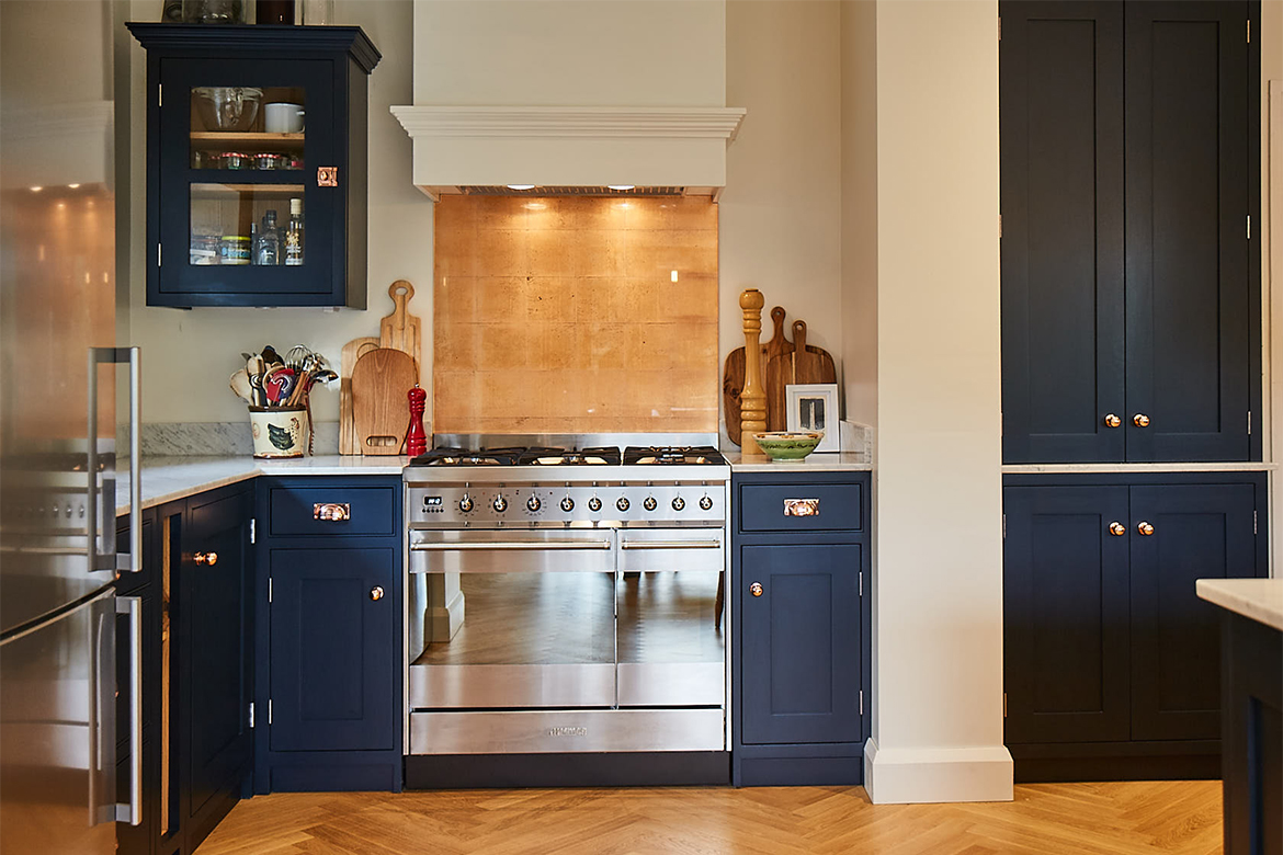 Freestanding range cooker with copper splash back and pained white extraction surrounded by low blue pained kitchen units