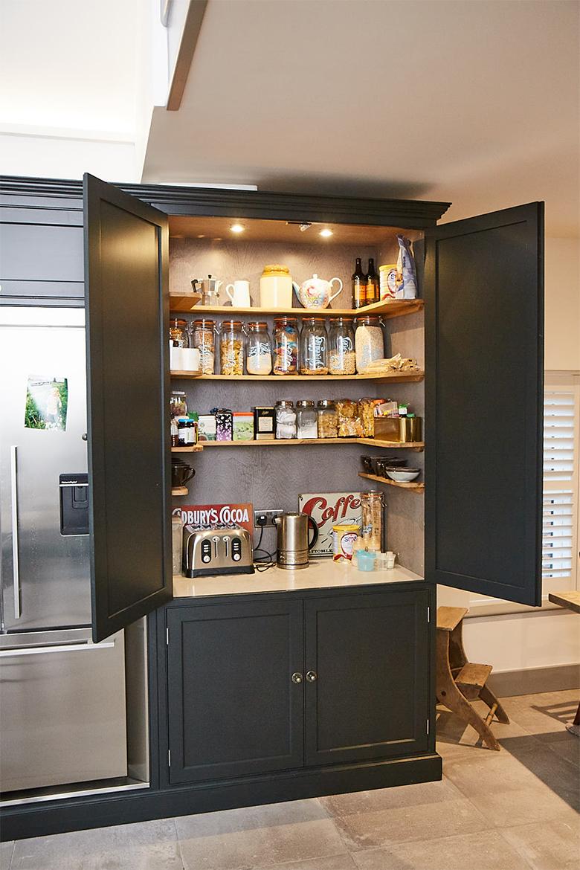 Bespoke painted black kitchen larder full with dry goods and working quartz worktop