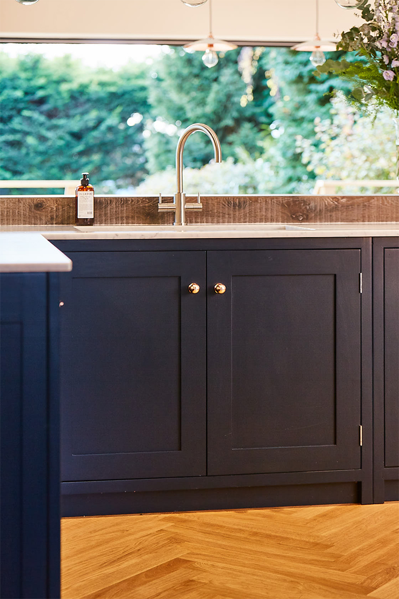 Dark blue double door shaker sink unit with stainless steel tap and cream quartz worktops