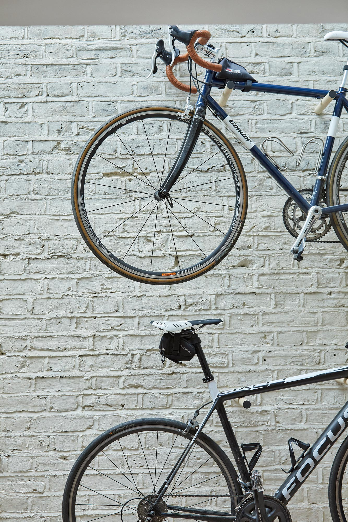 Bikes stored on painted white brick wall