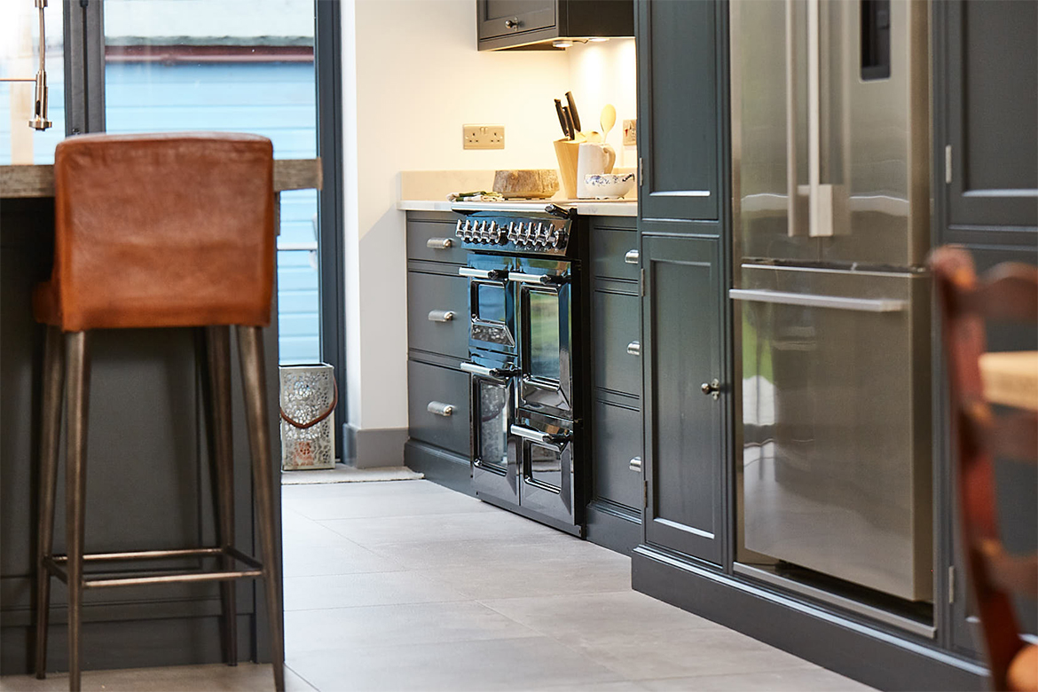 Black range cooker sits alongside fisher paykel stainless steel American fridge freezer and painted black units