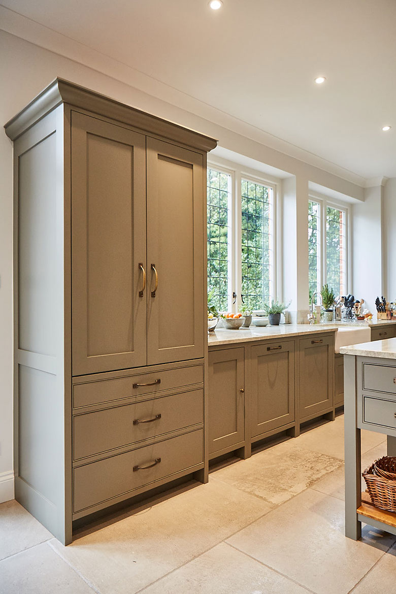 Tall traditional larder unit with large cornice next to crittall windows