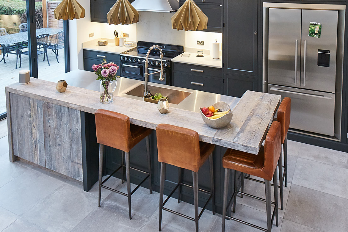 Large kitchen island with grey tiled floor and painted black units with contrasting stainless steel worktop