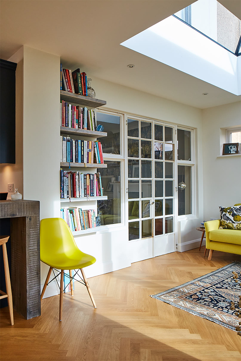 Living area with bookshelves next to large glass doors and oak parquet wood floor