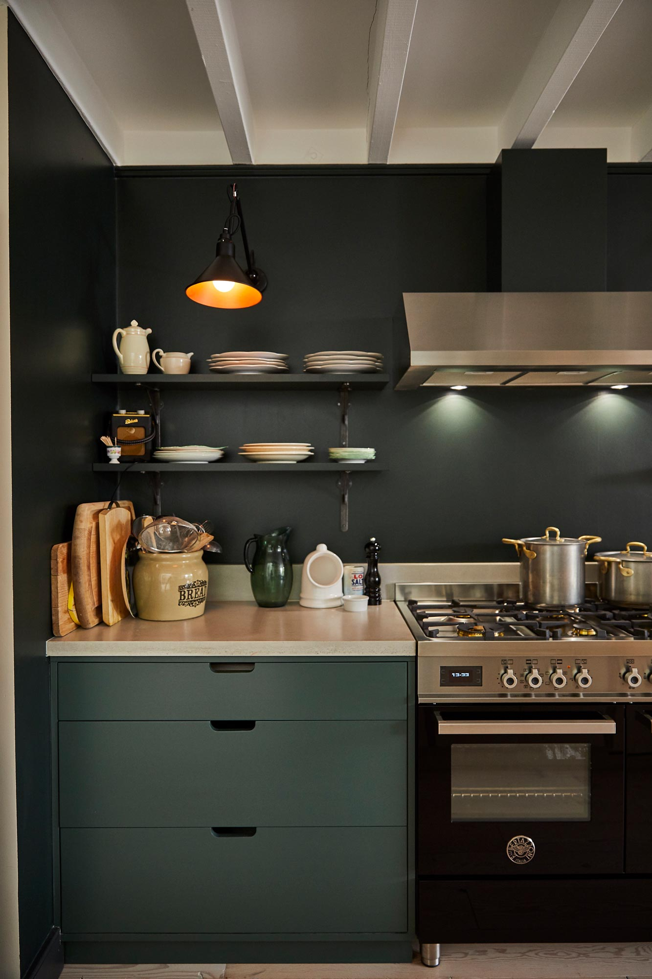 Green painted wall matches green painted pan drawer next to industrial range cooker