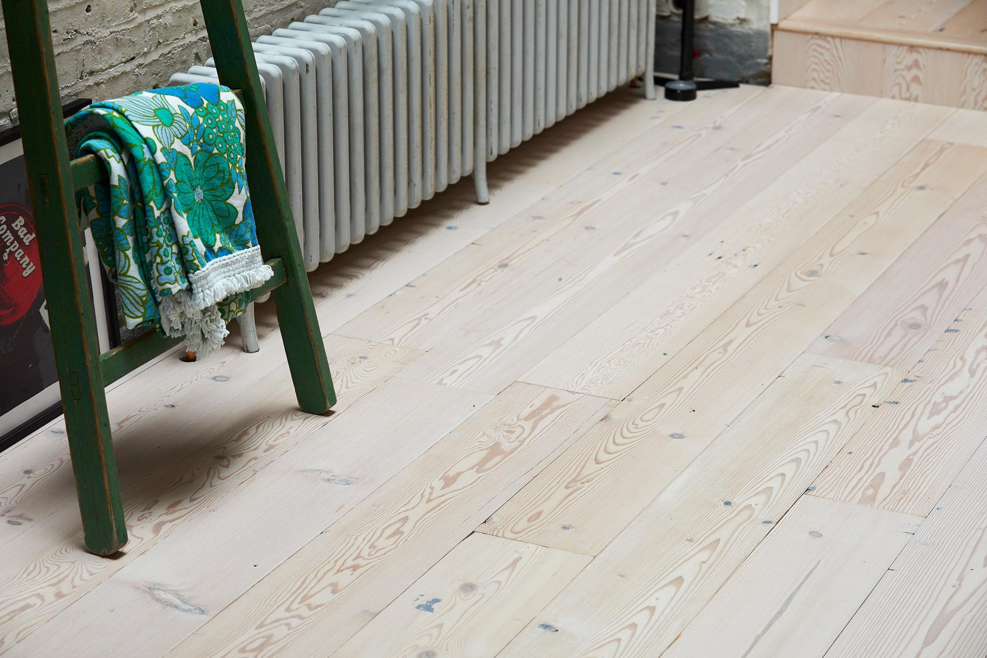 Whitewash pine flooring with green ladder