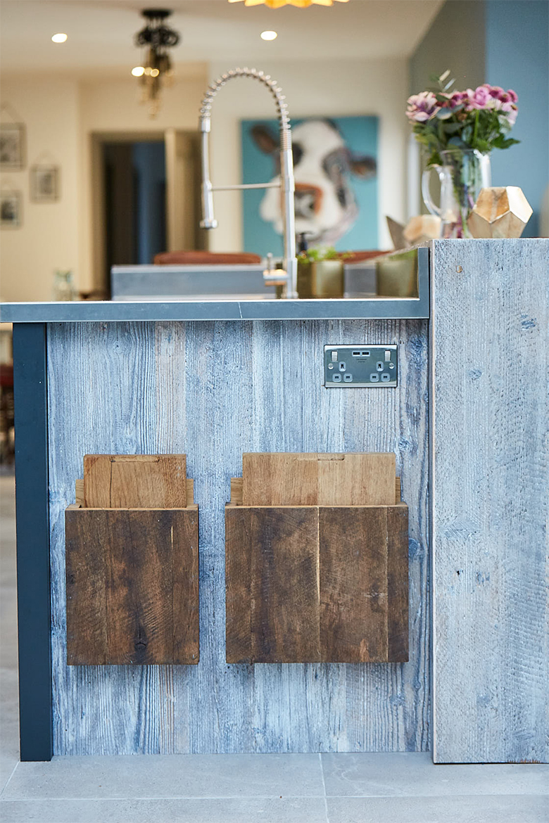 End panel of kitchen unit holds two oak chopping boards and has stainless steel plug socket mounted in to the side