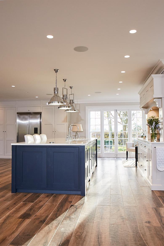 Chrome pendant lights over shaker blue kitchen island with Centaurus grey worktop