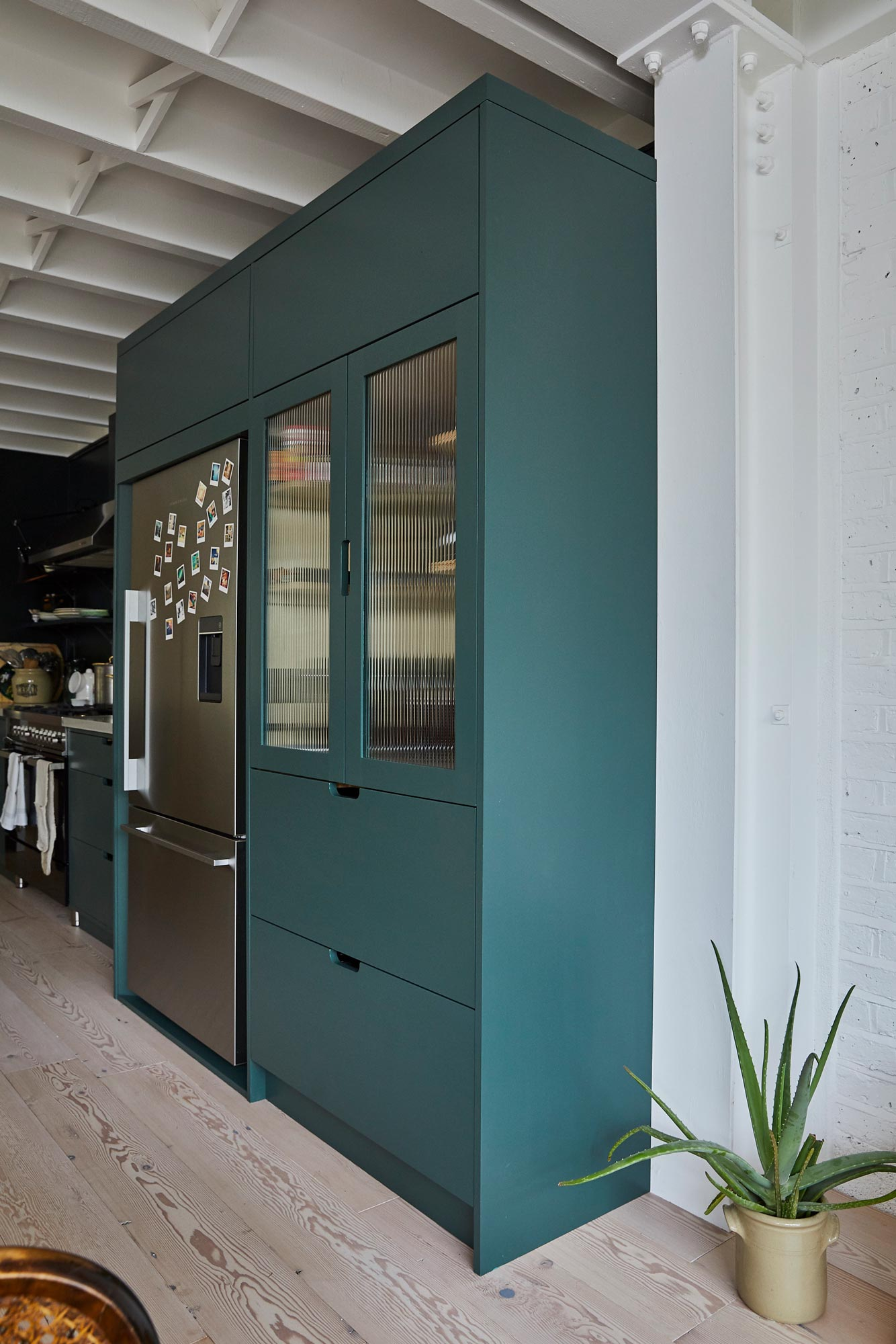 Green painted pantry unit next to stainless steel fridge freezer