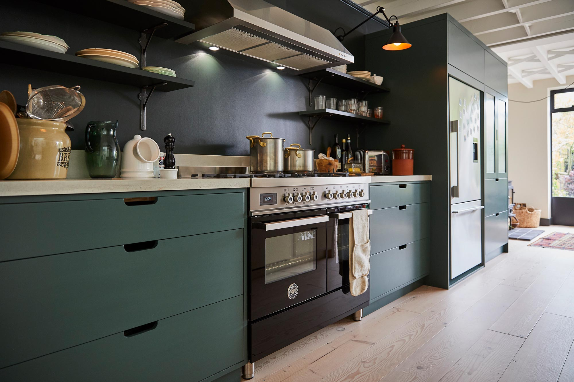 Range cooker next to painted birch plywood kitchen unit and concrete worktop