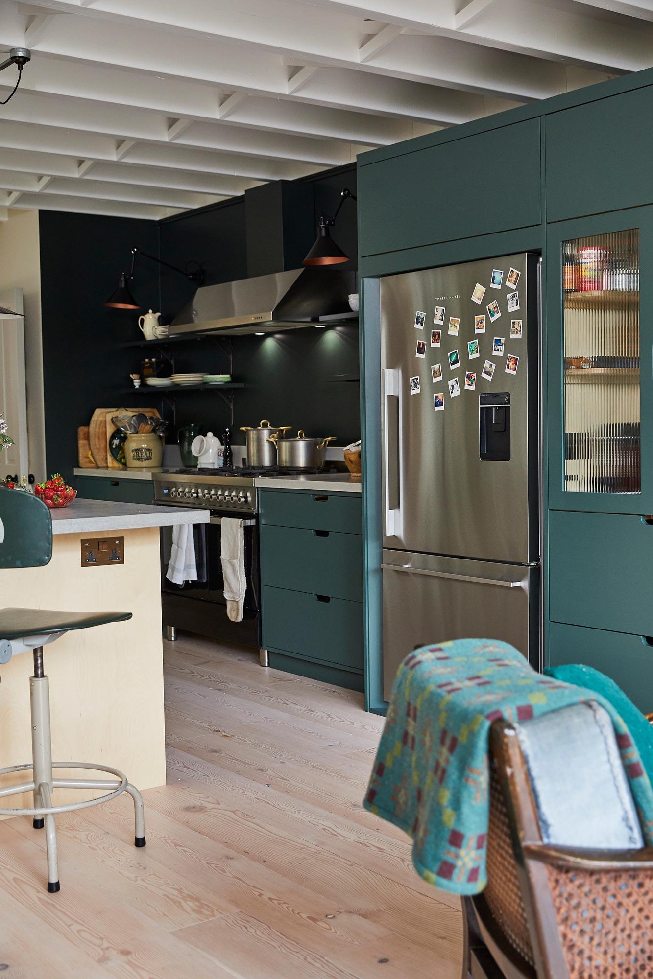 Freestanding stainless steel Fisher & Paykel fridge freezer in bespoke green kitchen