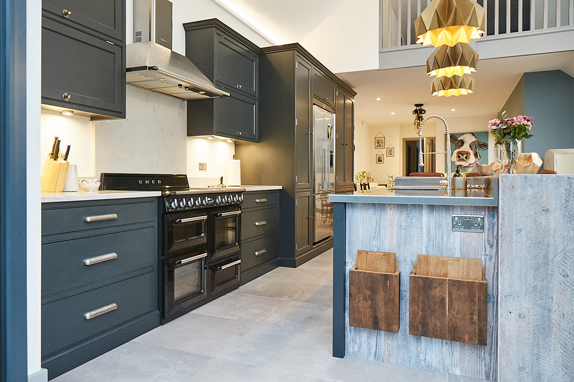 Black range cooker sits in between bespoke painted cabinetry featuring two large pan drawers