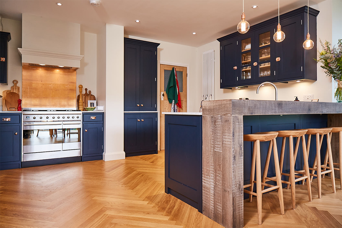 Hand aged chunky oak breakfast bar with dark blue painted cabinets under and clean oak bar stools