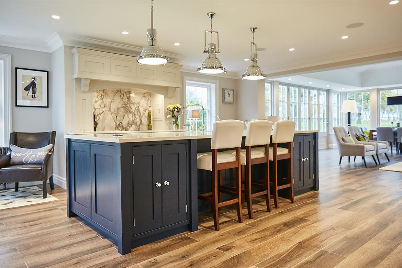 Blue shaker kitchen island with white leather barstools