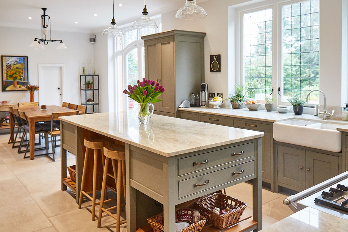 Oak breakfast bar stools sit under grey moss freestanding kitchen island with flowers on worktop