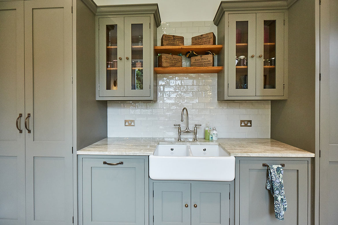 Belfast Sink unit against white metro tiles, glass wall cabinets, and open solid oak shelves