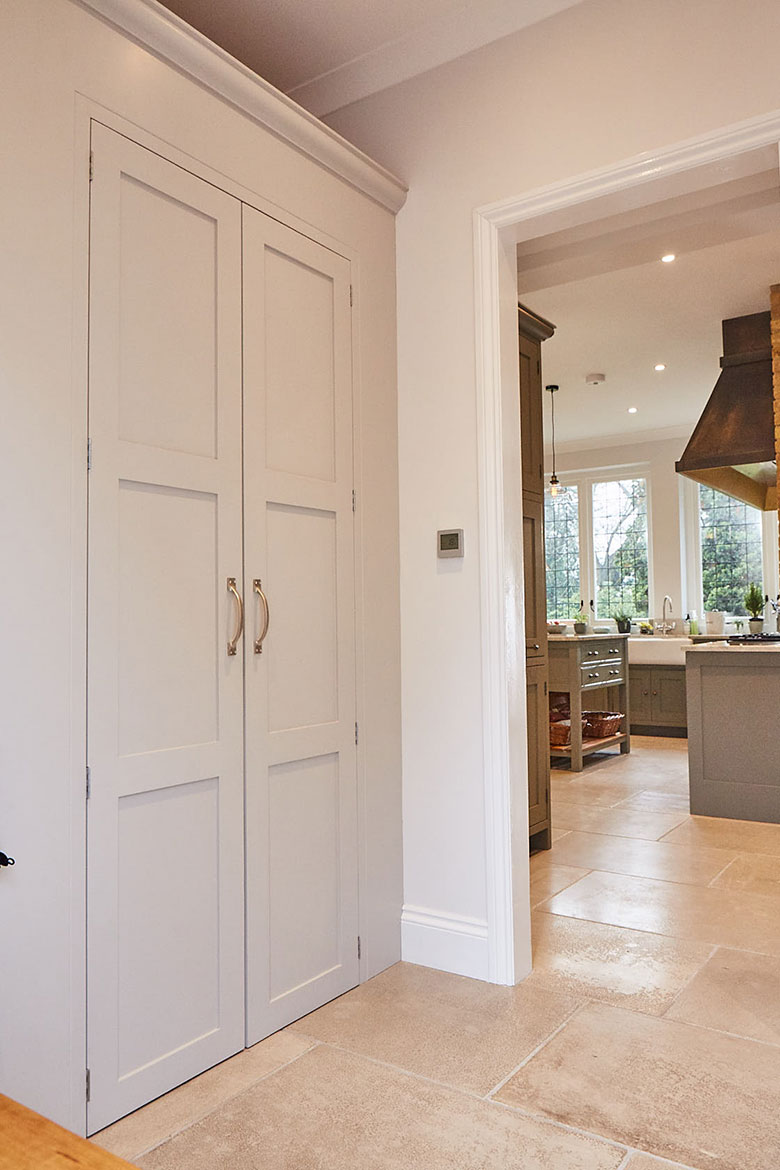 Tall Light painted cabinets with traditional finish and Croft brass pull handles