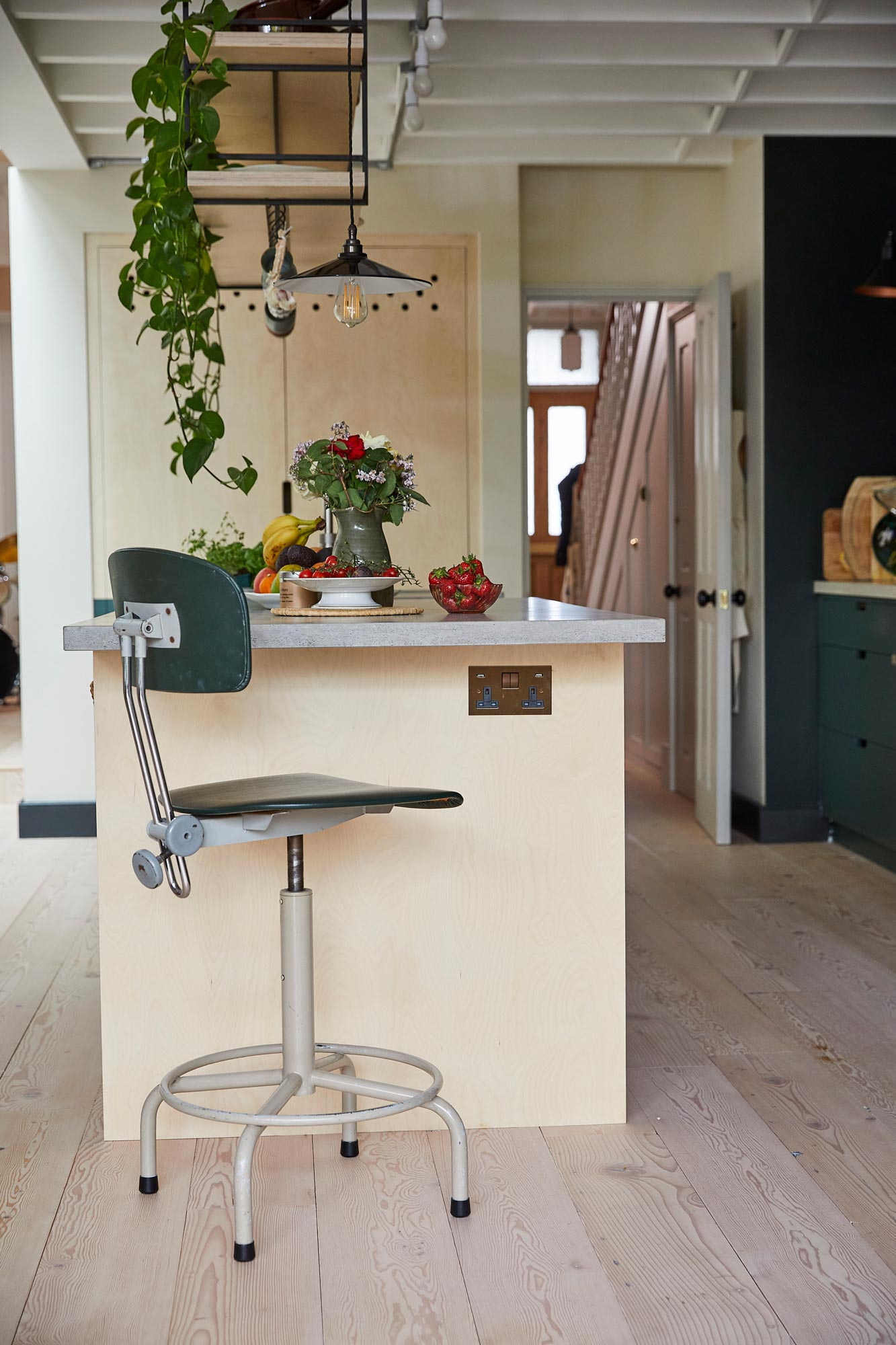 Industrial swivel green barstool under concrete breakfast bar