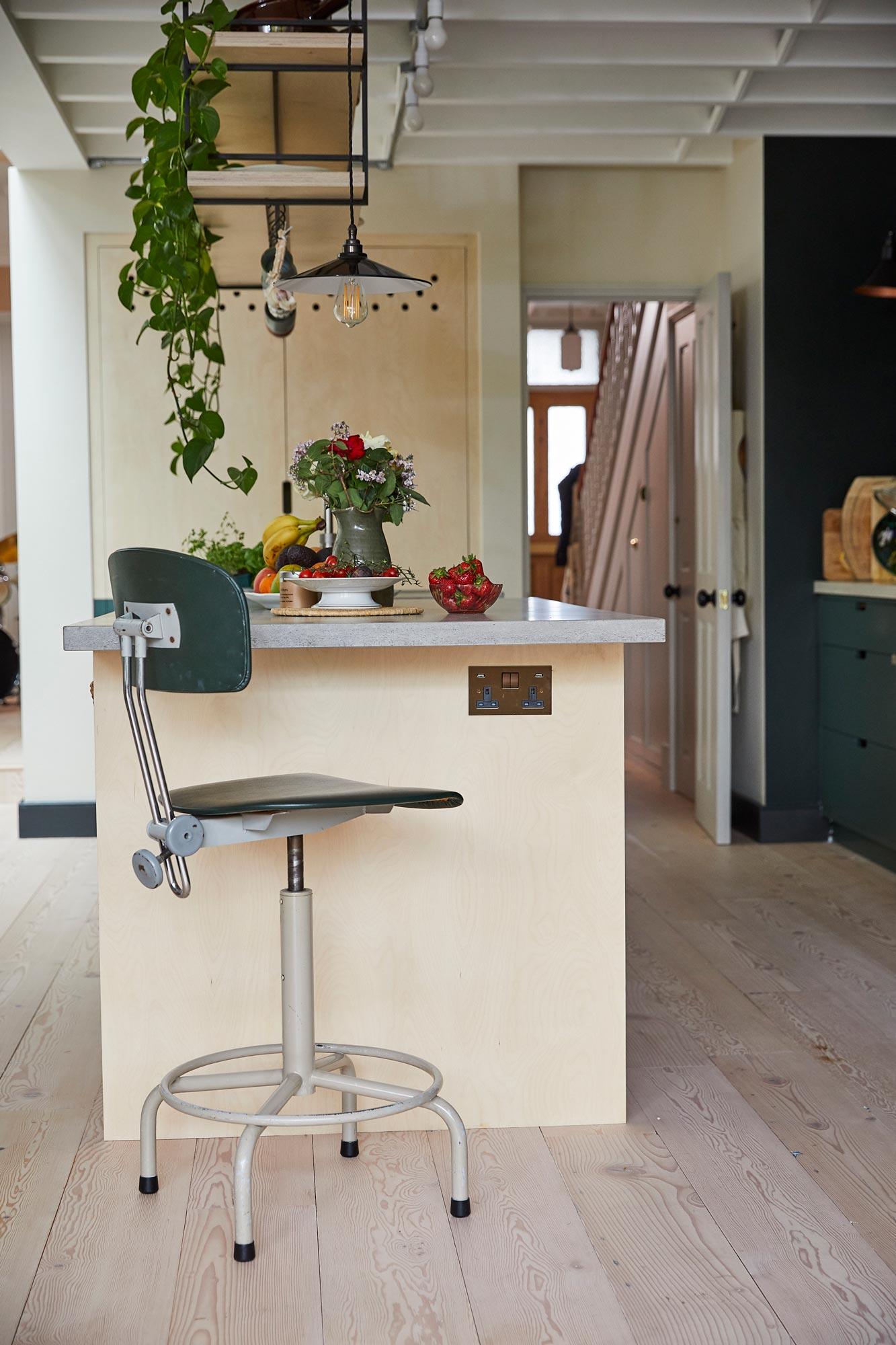 Industrial swivel green barstool under concrete breakfast bar