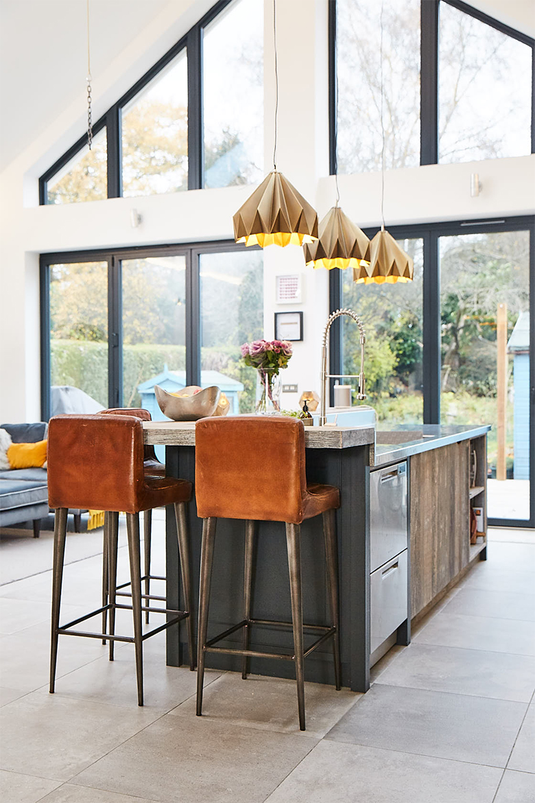 Large vaulted room with huge glass windows and reclaimed rustic painted kitchen island and brown leather chairs