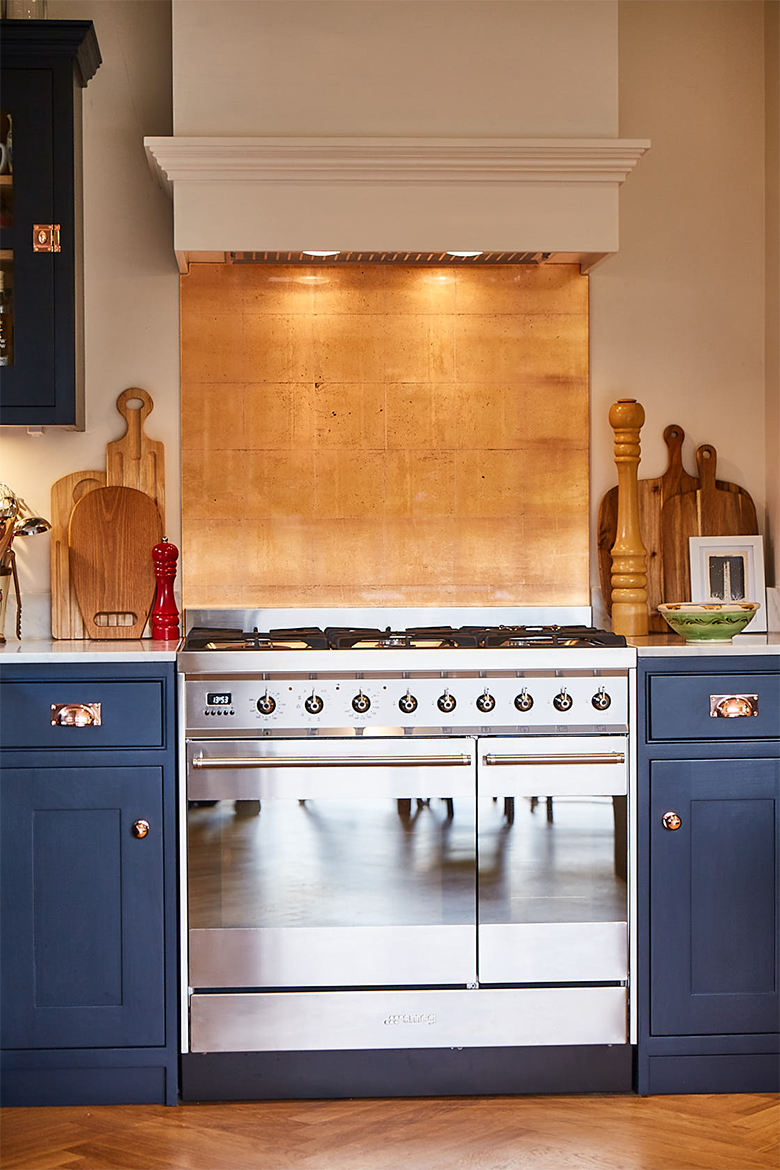 Stainless steel gas range cooker with copper splash back and pained white extraction
