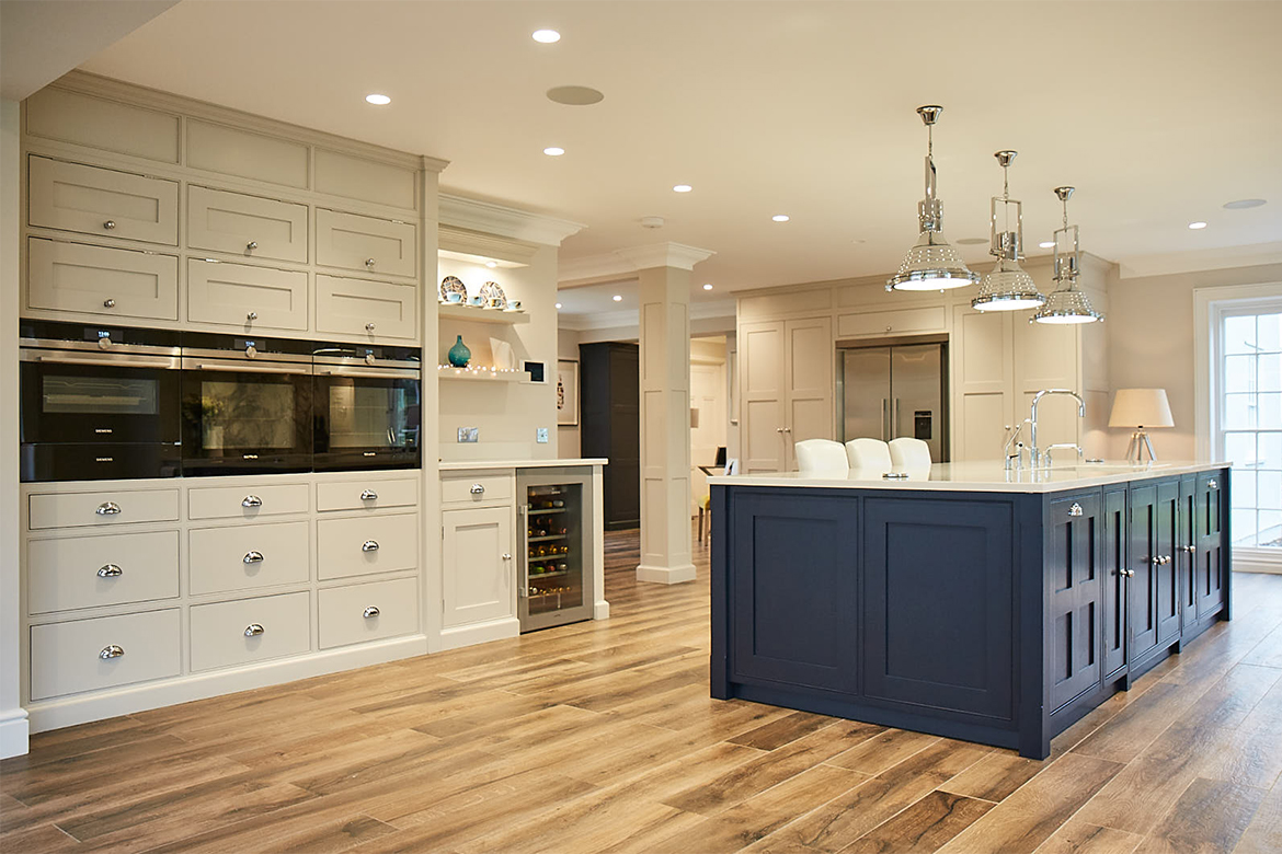 Eye level ovens in bespoke painted light grey kitchen cabinets behind blue island