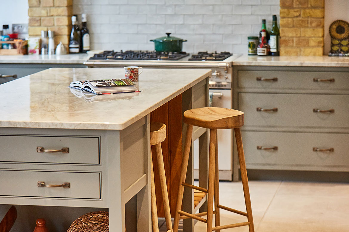 Cook book rests on granite worktop with oak bar stool pulled out
