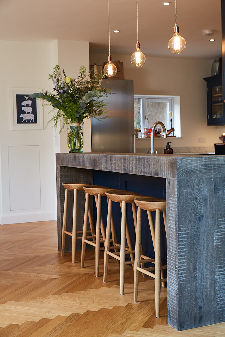 4 clean oak bar stools sit on parquet wood floor under hand aged chunky breakfast bar with blue back panel