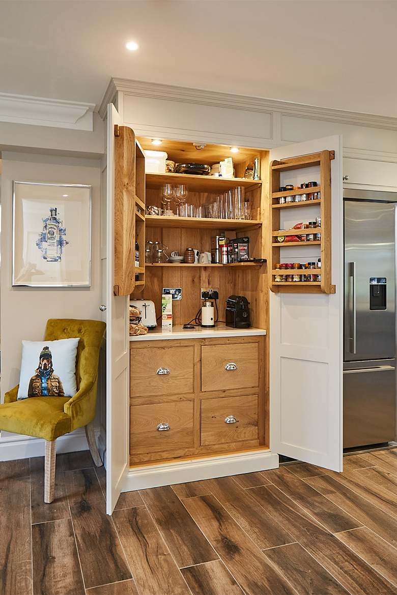 Tall larder unit open with solid oak internals including 4 drawers with quartz worktop and racks on each door