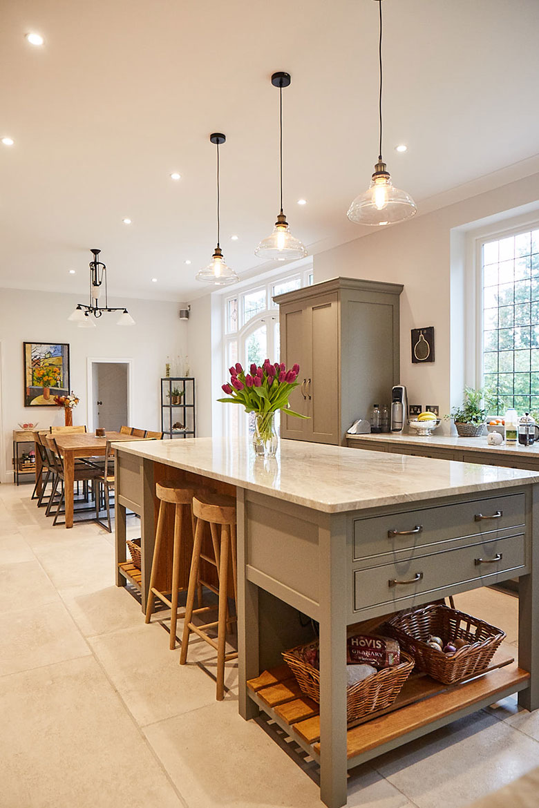 Bespoke kitchen island painted grey moss with granite worktop and glass pendant lights above