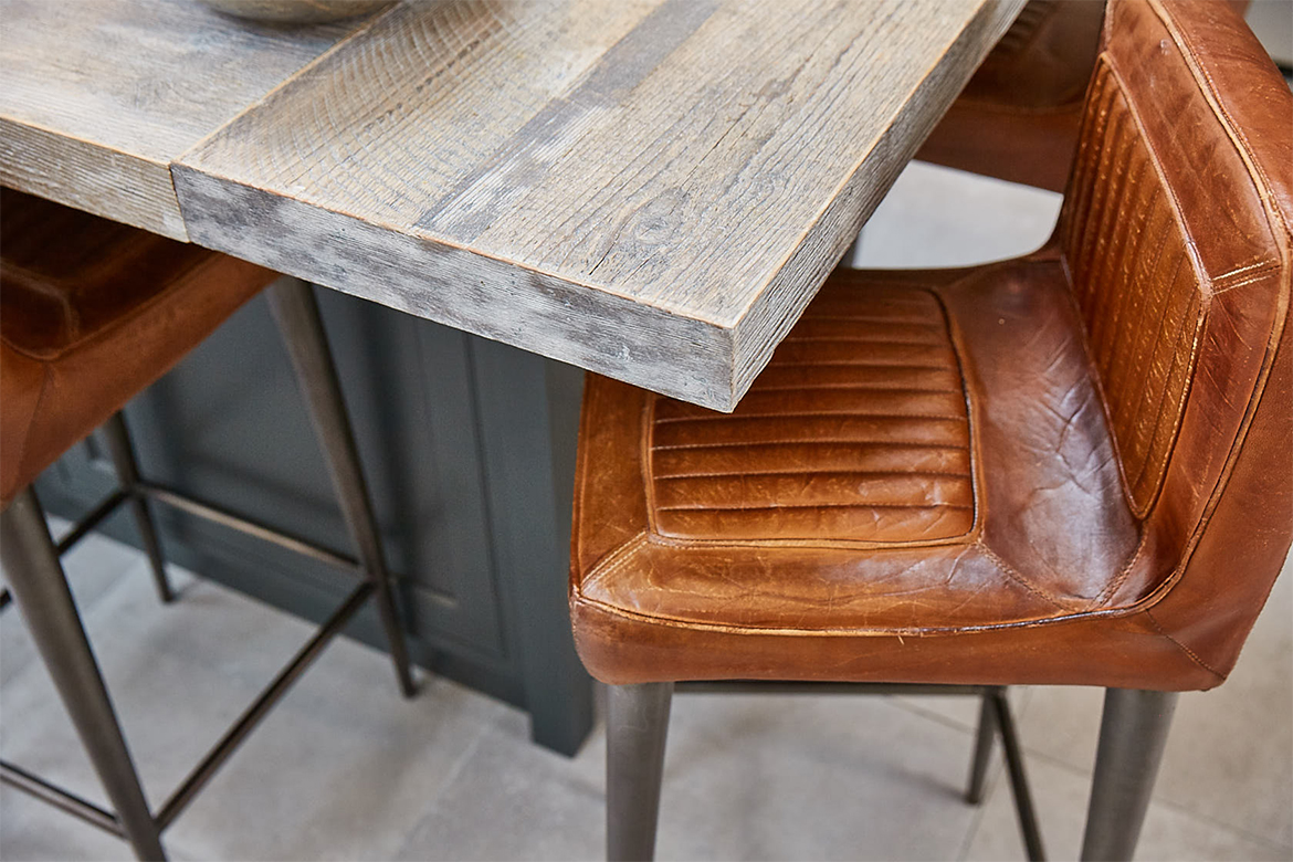 Engineered reclaimed rustic kitchen worktop with brown leather bar stools