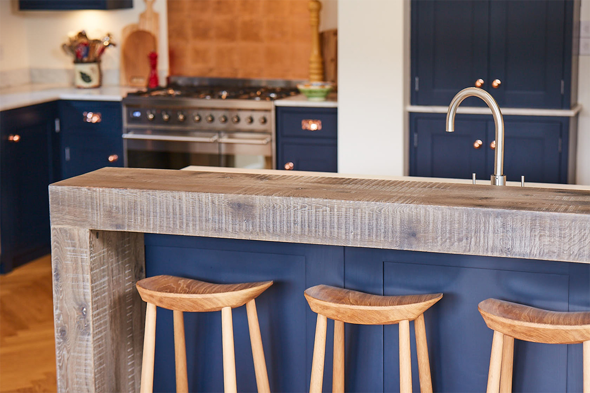 Engineered oak breakfast bar with blue painted back panel and oak stools