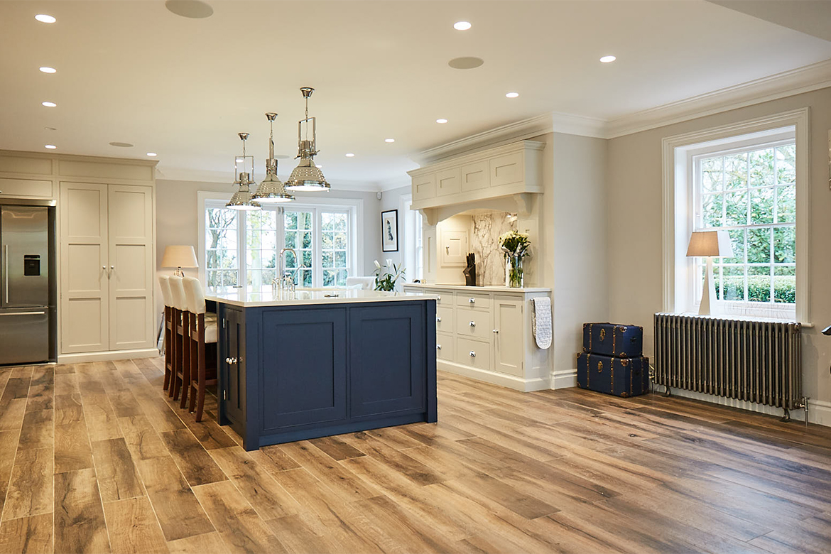 Painted shaker blue kitchen island with large chrome pendant lights above