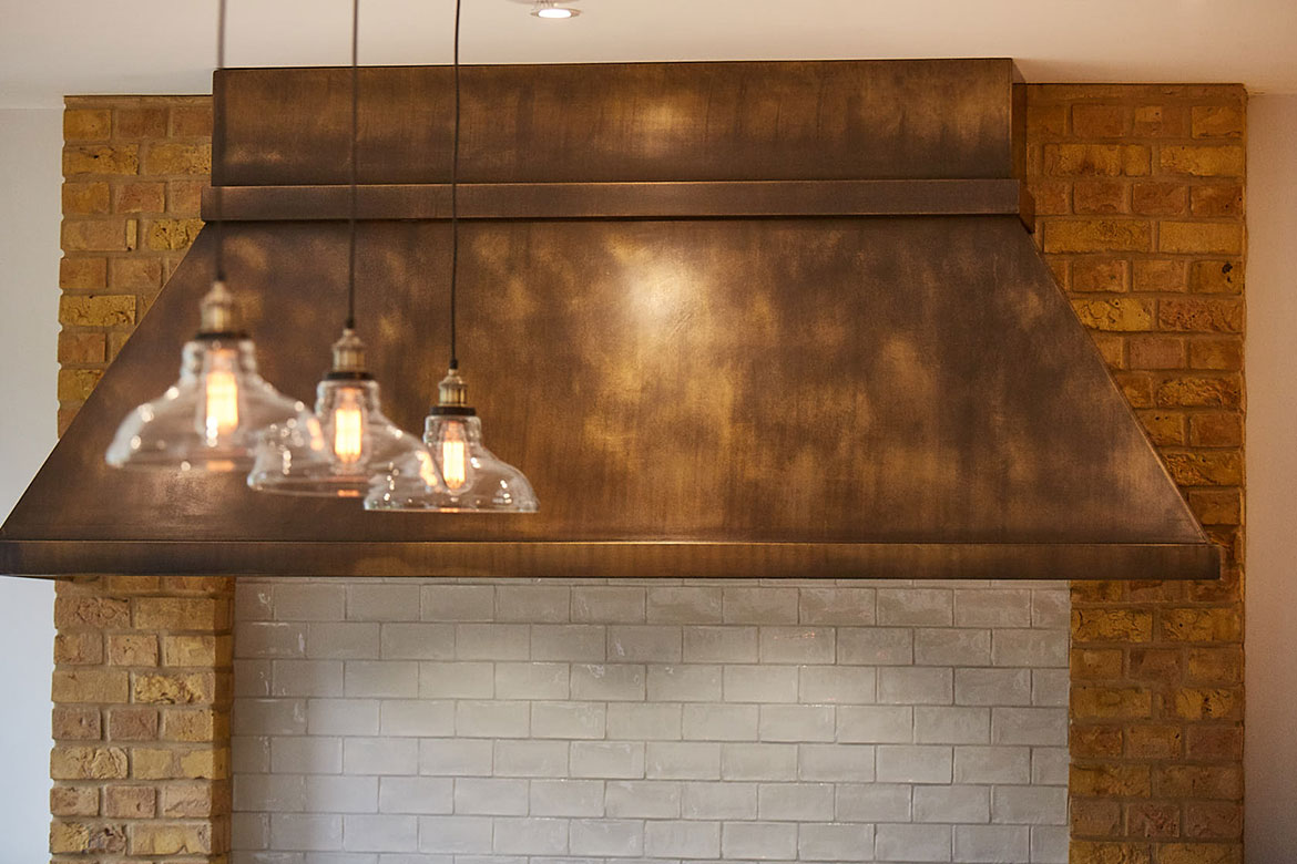 Glass pendant lights shine on aged brass bespoke canopy for extractor